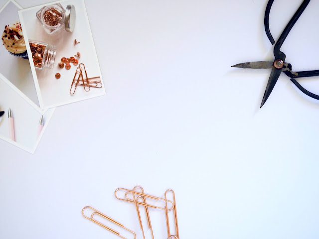 Crafting supplies (a pair of scissors, pins, clips) displayed and shot flatlay-style.