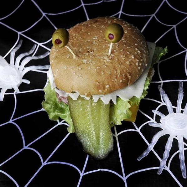 una hamburguesa con una loncha de pepino gigante, a modo de lengua y dos aceitunas clavadas en la capa superior que recuerdan ojos