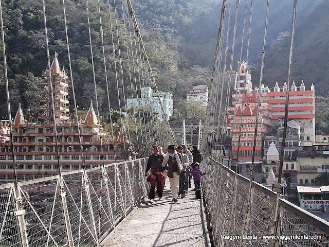 A ponte Laxman Jhula e os templos e Ashrams ao fundo, em Rishikeshi