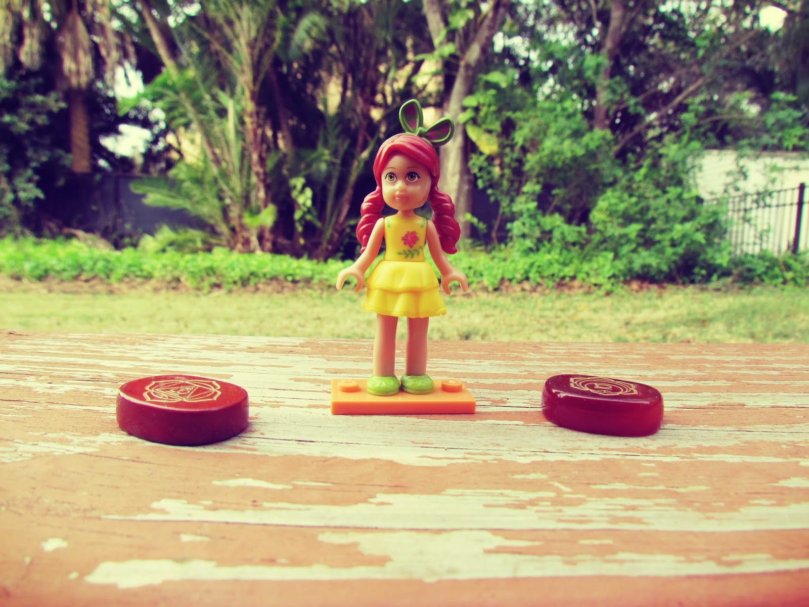 A tiny American Girl Doll Figurine on the back porch in a tropical style backyard setting