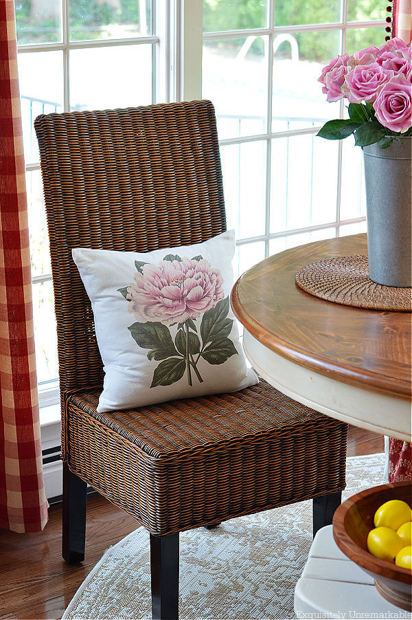 Wicker Parsons Dining Chair with floral pillow around table