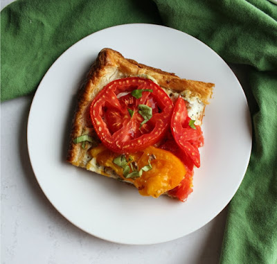 slice of tomato tart with red and yellow tomatoes, puff pastry, ricotta and basilserved on plate.