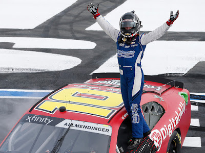 A J Allmendinger celebrates on the frontstretch after winning the NASCAR Xfinity Series Drive for the Cure 250 presented by Blue Cross Blue Shield of North Carolina at Charlotte Motor Speedway.
