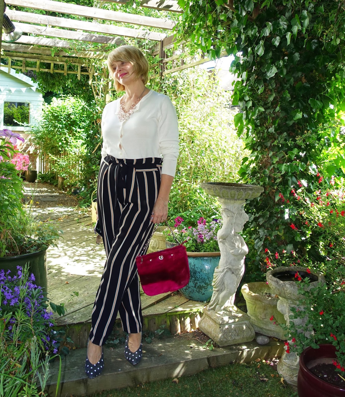 Garden shot of woman in striped paper bag trousers and cream cardigan