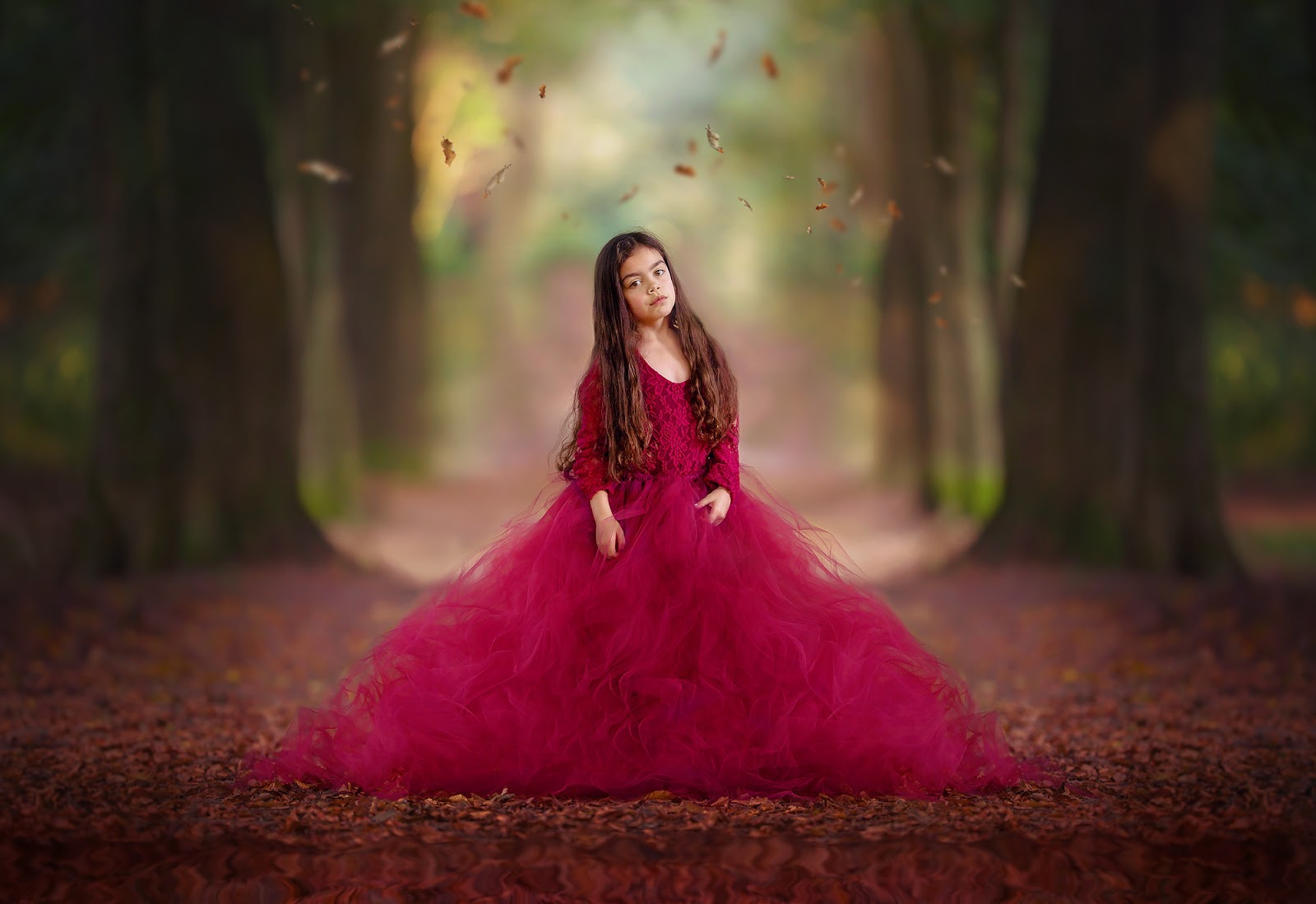 Canon 200mm portrait of a young girl in a beautiful red dress standing in an autumn forest with falling leaves above her head by Willie Kers
