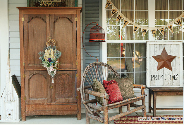 This country style front porch decor is a little bit rustic with a gorgeous wooden armoire and pallet art