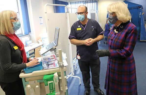 Duchess of Cornwall is wearing a face-mask and protective glasses. The Duchess wore a tartan coat dress, and a printed pattern scarf from Seasalt