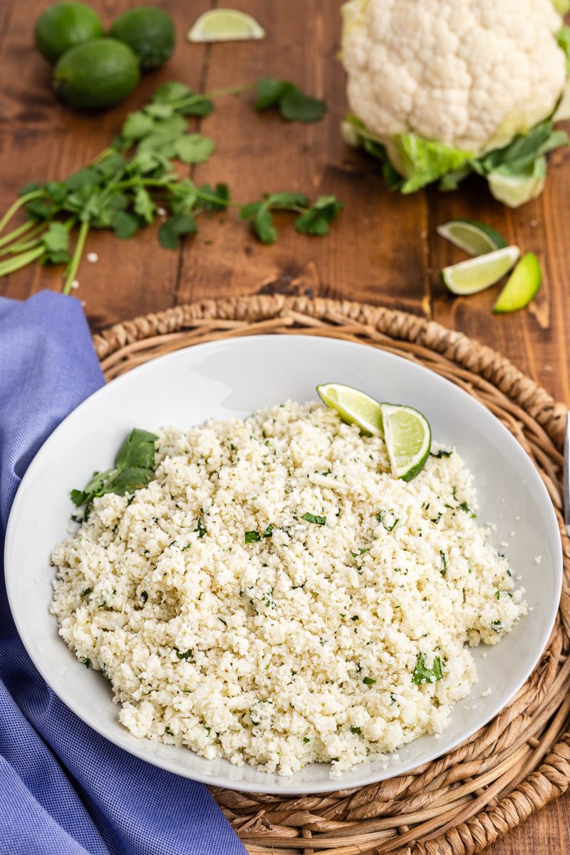 Photo of Copycat Chipotle Cilantro Lime Cauliflower Rice in a serving bowl on a wooden table.