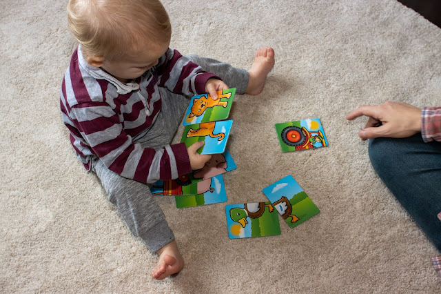 A toddler with the Farmyard heads & Tails game working out how to put the 2 cat cards together