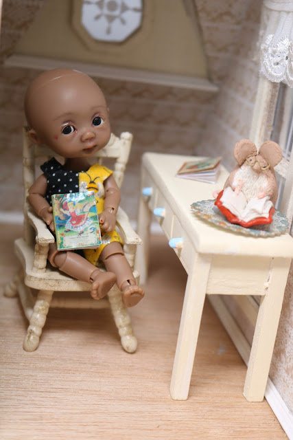 Alma the doll enjoys her new book of nursery rhymes
