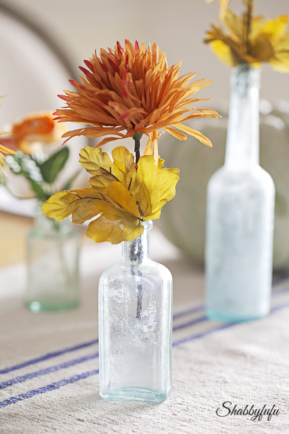 vintage aqua bottles filled with flowers in rust for thanksgiving