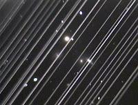 Fot. 2. Zdjęcie grupy galaktyk NGC5353/4 wykonane za pomocą teleskopu w Obserwatorium Lowell w Arizonie, w nocy z soboty 25 maja 2019 r. Ukośne linie biegnące wzdłuż obrazu to ślady odbitego światła pozostawionego przez ponad 25 z 60 niedawno wystrzelonych Starlinków, gdy przelatywały przez niewielkie pole widzenia teleskopu. Chociaż ten obraz służy jako ilustracja wpływu odbicia światła słonecznego od konstelacji satelitów, należy pamiętać, że gęstość i skupienie tych satelitów jest znacznie wyższa w pierwszych dniach po wystrzeleniu, jak obrazuje to zdjęcie, a także że satelity będą zmniejszać jasność, gdy osiągną swoją końcową wysokość orbity. Credit: Victoria Girgis/Lowell Observatory