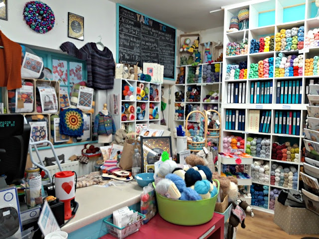 A photo showing the interior of a yarn shop.  In the foreground is a green bucket full of balls of yarn and a shop till with various accessory items on the counter.  Behind the counter, displayed on a wall to the left, are knitted garments and knitting kits.  On the other walls at the back and to the right of the photo are shelves containing balls of yarn and folders containing individual knitting patterns.