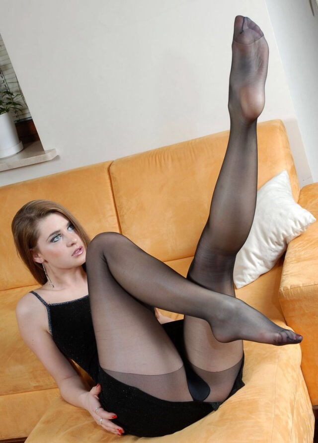 Woman In Red Pumps And Black Stockings Is Sitting With Parallel Legs Stock Photo