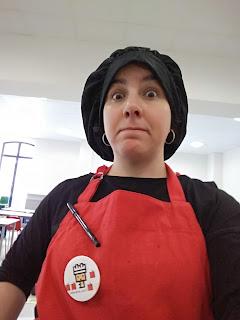 pongo cara de susto, llevo gorro de cocinera negro y un delantal rojo con una chapa del blog. estoy en un comedor infantil