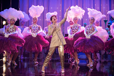 Judy Garland (Renée Zellweger) singing on stage in a gold outfit surrounded by showgirls in the film Judy (2019)