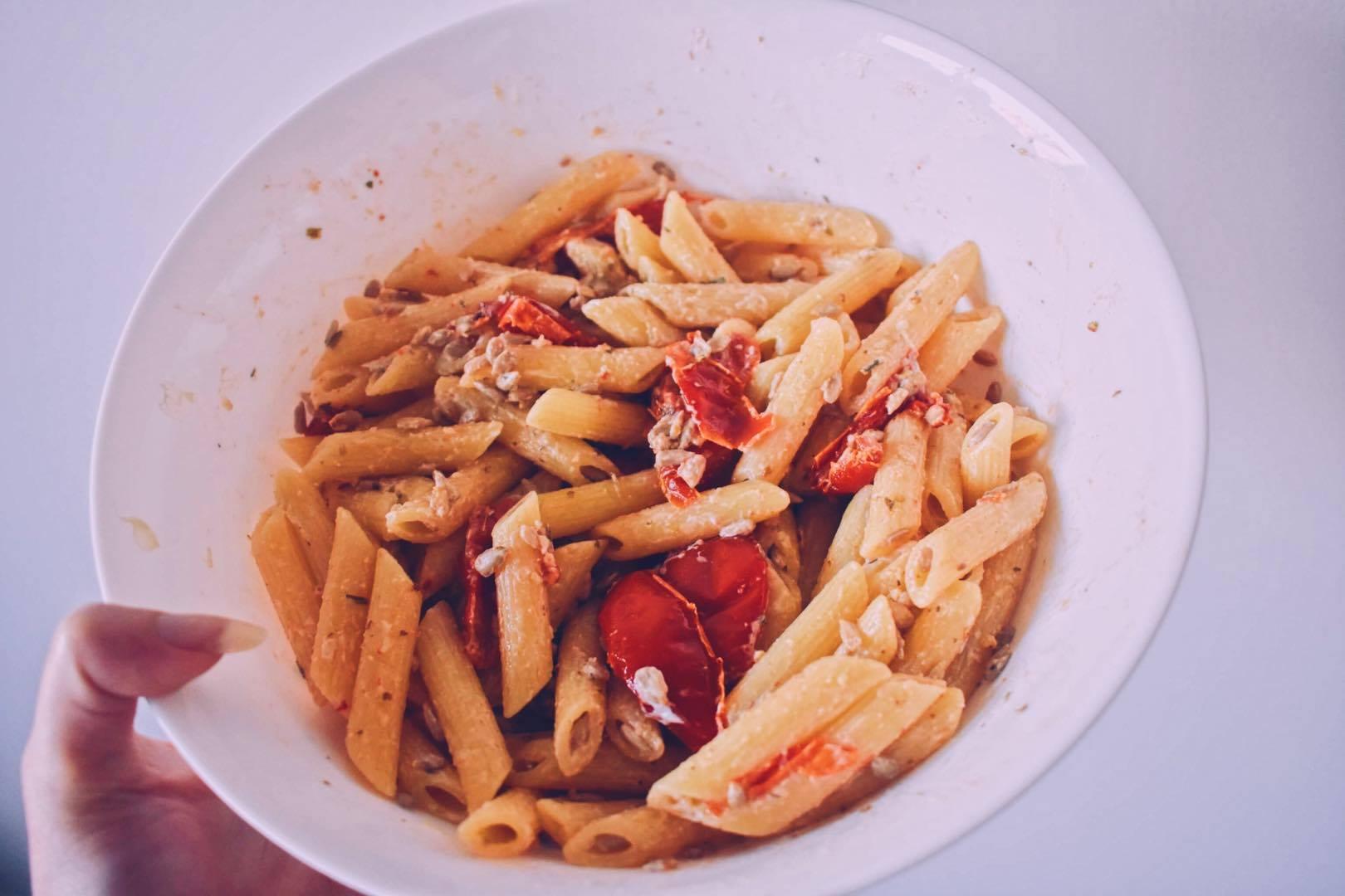 Pasta met zongedroogde tomaatjes, roomkaas en zonnebloempitten gemengd in een witte kom.