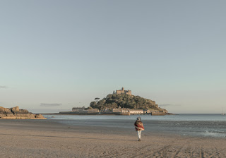A girl stands on an empty beach, with a view of St Michael's Mount ahead of her.