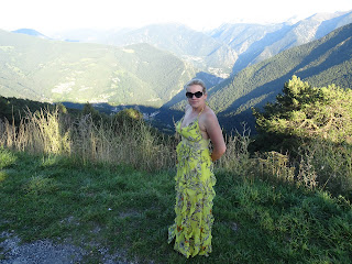 mountain in back ground woman posing in flowing yellow dress