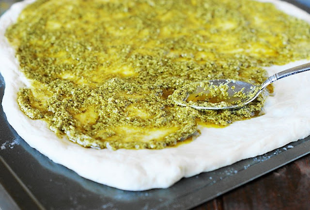Spreading Pesto as Sauce on Pizza Dough Image