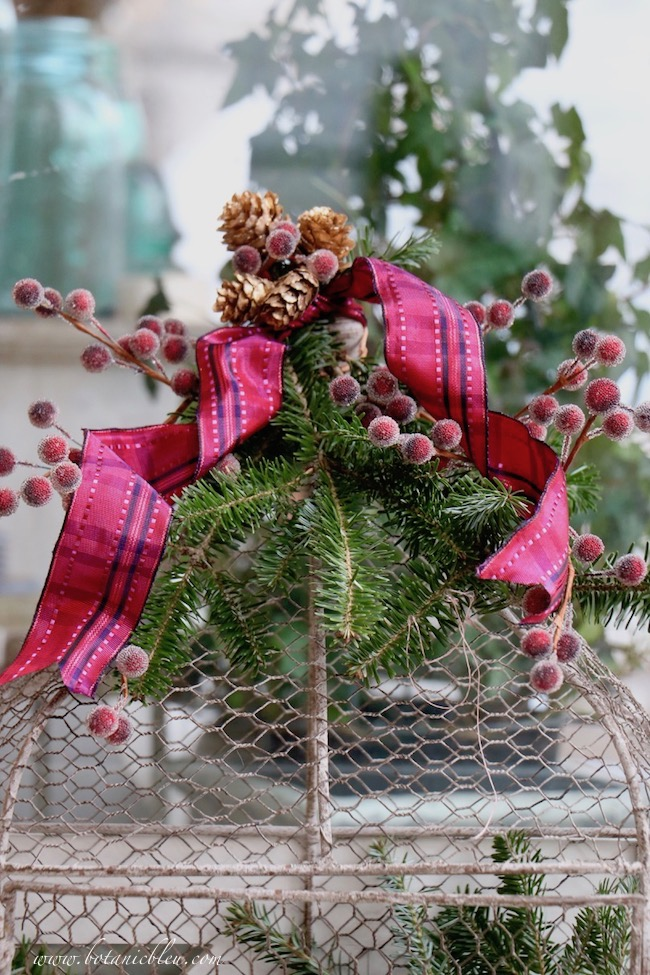 Decorate a Christmas red plaid berry birdcage with fresh greenery cut from a second-quality small fresh tree