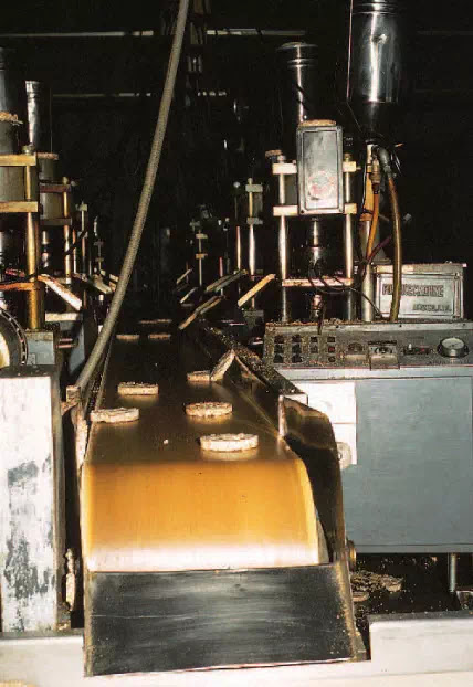 Figure 1A Rice cakes food being manufactured. Unprocessed rice is poured into small ovens where the kernels are expanded. The kernels are then compressed into cakes, which are conveyed by belt to a packaging area.