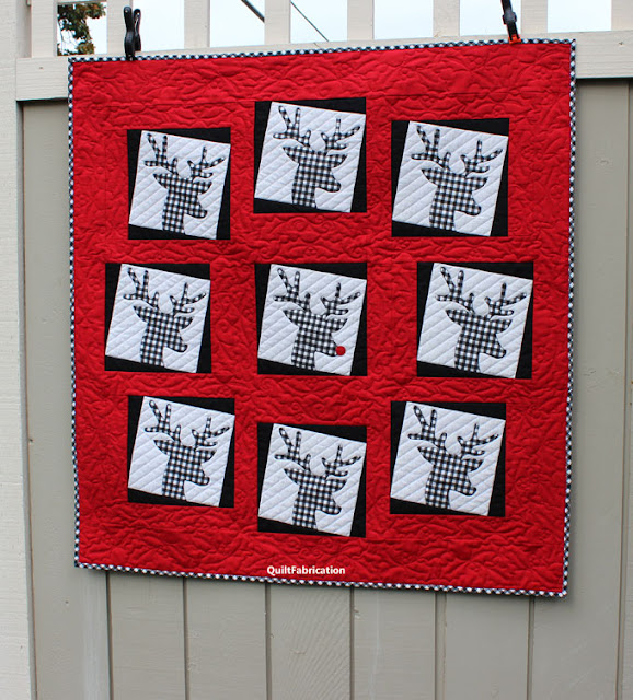 black and white checked deer heads in a circle with Rudolph in the middle all on a red background by QuiltFabrication