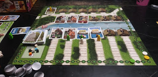 The game board, with a game in progress. The board has two sections: on the top, two rows of huts serve as places for cards. The top row has only one card, with a yellow meeple on it. The bottom row has three cards, with no meeples. The bottom half of the board has a row of huts, four of which have cards on them. In front of each hut is a path divided into spaces leading up to the hut. The path leading to the first hut is empty. There is a single green meeple on the path to the second hut. The third hut has both a green and a white meeple on the path. The fourth hut has a yellow meeple on its path. The cards have artwork representing Viking warriors, crafters, traders, and sailing ships. The cards representing ships have one to three wooden cubes of different colours on them. In the corner of the board is a space for the deck of cards, and another space holding several additional coloured wooden cubes. Along the edge of the board is a scoring track, with a green, white, and yellow disc at various points along it. On the table near the board are a stack of tokens representing coins and a player's board with some unused meeples and a variety of cards around it.