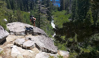 Hiker who is also a photographer climbing to the top of a large stone cliffside with a river below