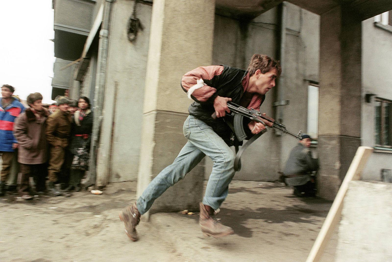 An anti-Communist civilian fighter armed with a Kalashnikov AK-47 chases the supposedly Securitate secret police agents loyal to the communist power during a street-fighting.