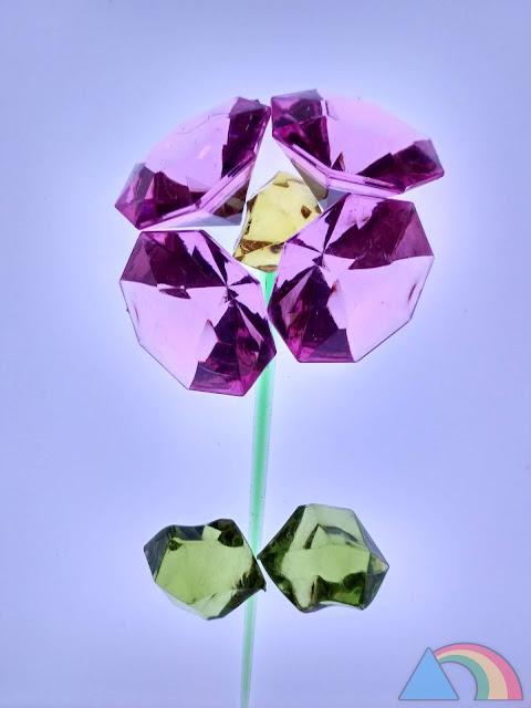 Flor hecha con piedras decorativas sobre mesa de luz