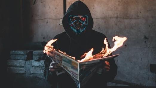 フードを被り顔面マスクをした怪人が燃える新聞を読んでいる
