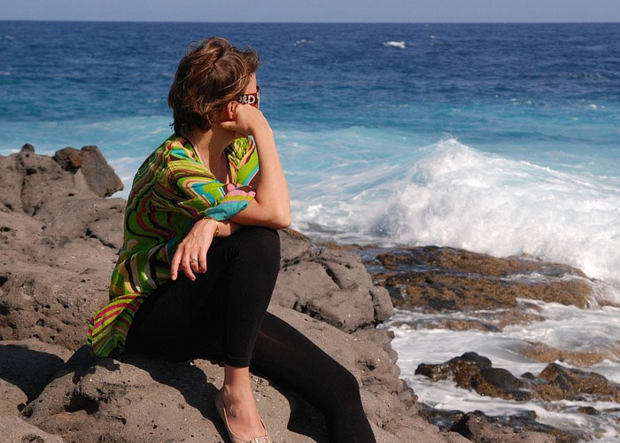mulher de frente pro mar pensando porque ela nunca deu certo com ninguém