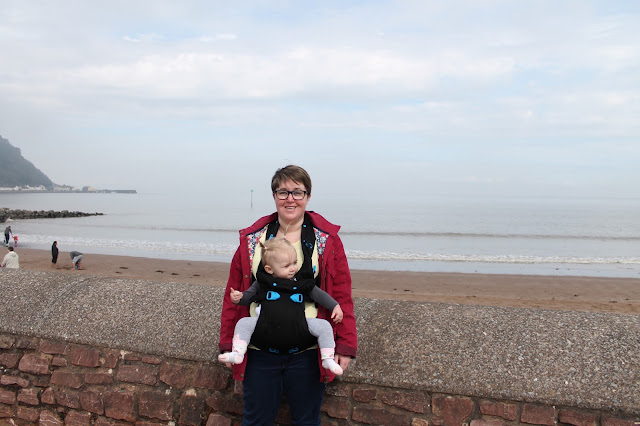 mother with baby in pao papoose baby carrier at Minehead beach opposite Butlin's