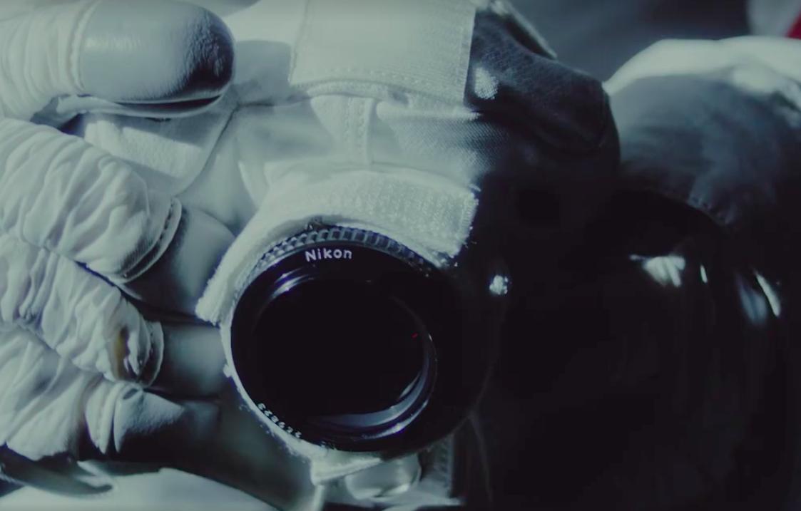 Nikon Kamera und Objektiv in den Händen eines Astronauten - Man sieht die Handschuhe und die eingepackte Kamera in weißem Thermostoff auf dem Objektiv steht Nikon