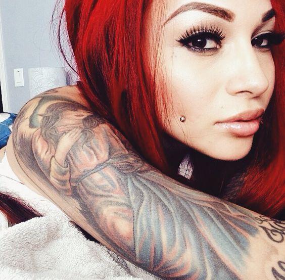 Preciosa mujer peliroja, acostada nos mira tiernamente, lleva tatuaje de un angel en el brazo