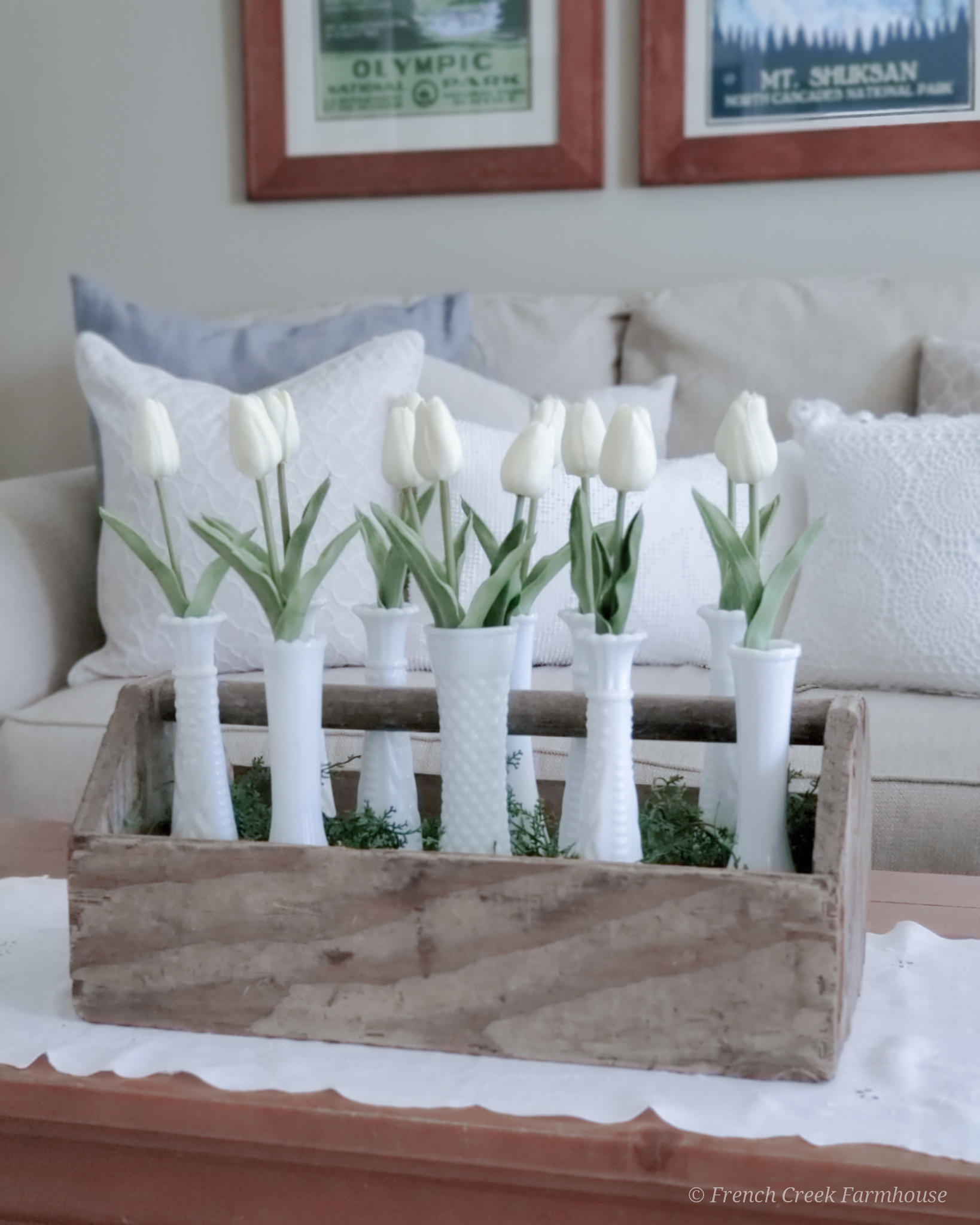 Modern farmhouse spring living room with white tulips in milk glass vases