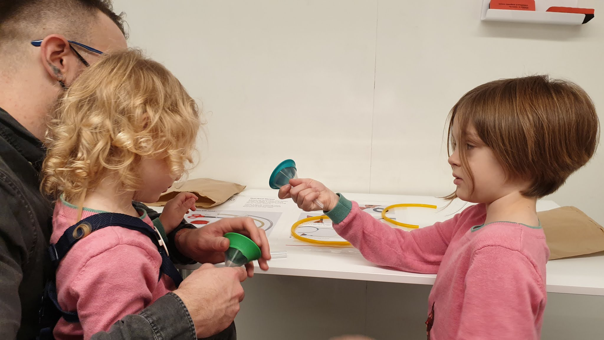 two kids making a stethoscope craft
