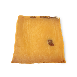 A bright orange slanted square piece of soap with lush engraved on the side of it on a bright background
