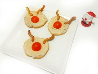 Tres tostadas con medio cherry en centro , parece la nariz de Rufolf arriba en borde los dos cuernos son galletas saladas