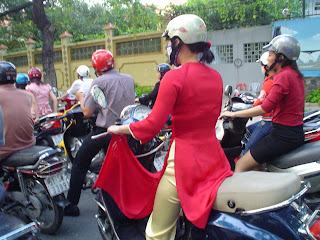 Modernity and tradition in Ho Chi Minh City - bike Vietnamese girl in costume