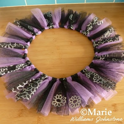 Black, purple and silver glitter fabrics tied around the wire base