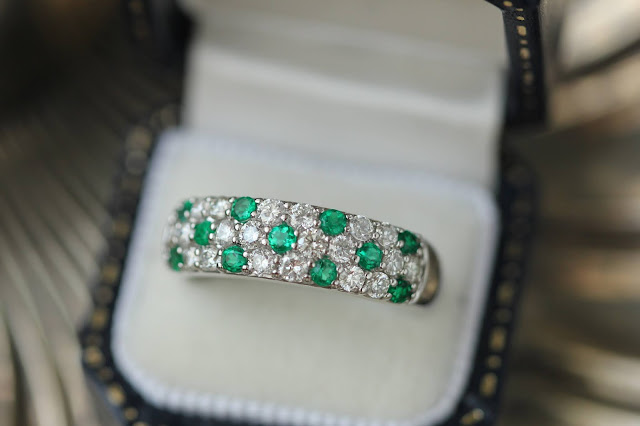 A ring with green and clear gemstones inside an open ring box.
