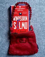 Kirja lattialla, sitä ympäröi punainen käsilaukku jalokivien näköisine hihnoineen