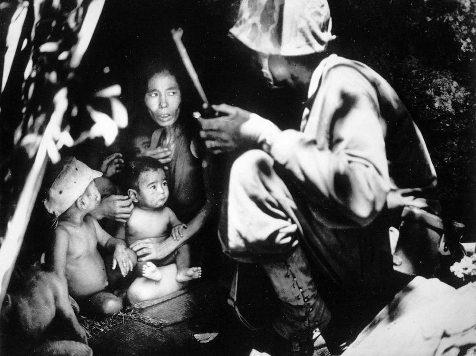 A member of a U.S. Marine patrol discovers this Japanese family hiding in a hillside cave, June 21, 1944, on Saipan. The mother, four children and a dog took shelter in the cave from the fierce fighting in the area during the U.S. invasion of the Mariana Islands.
