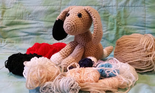 A crocheted dog sits surrounded by small balls and skeins of scrap yarn in different colours. The dog is light brown with a black patch on one ear and white patches on two feet and on its tail.