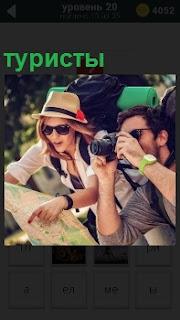 На отдыхе на экскурсии находятся туристы и фотографируют с рюкзаками за спиной и картой в руках