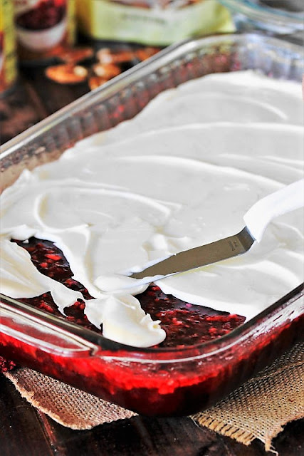 Spreading Topping on 7-Up Cranberry Jello Salad Image