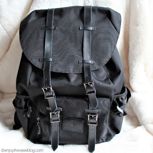 The American Shield Granite 25 backpack in black sitting on an ivory furry rug