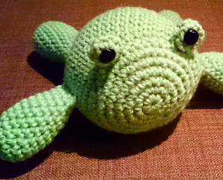Crochet frog plushie made with acrylic yarn in pale green. The design is different to the others, the body an oval shape with floppy limbs out the sides with to little nubbins for eyes, with safety button eyes attached.
